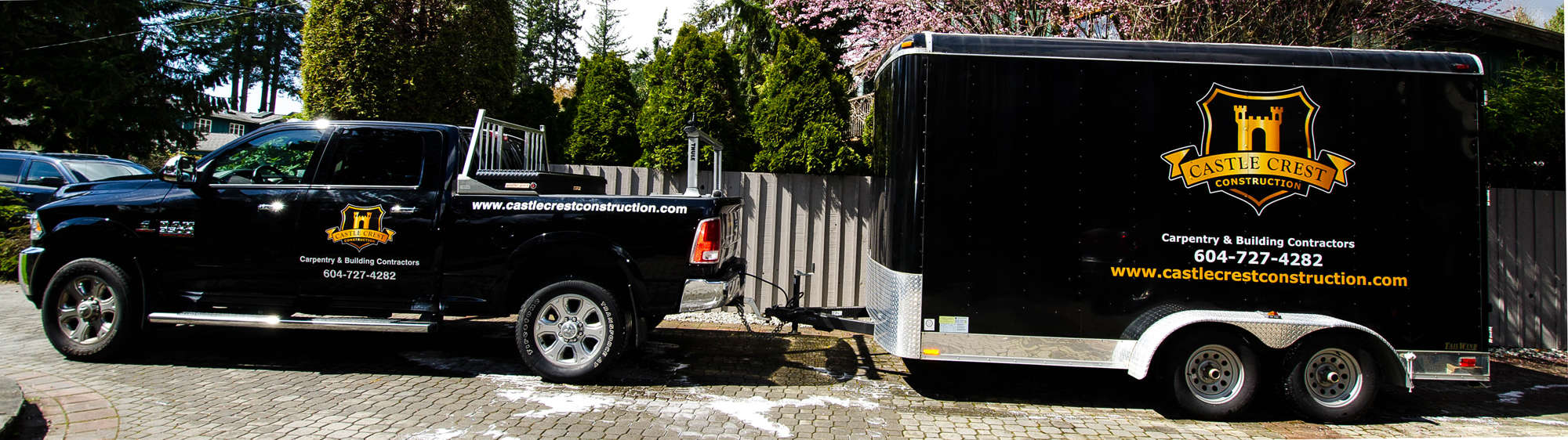 Black truck and trailer with Castle Crest Construction logo and contact information painted on the side.