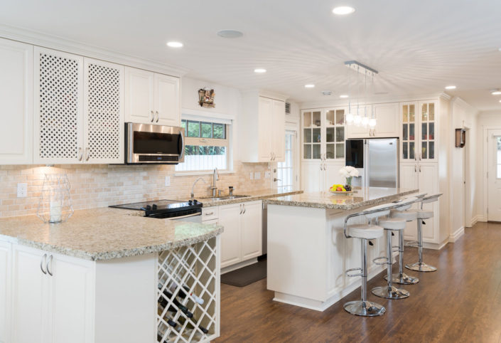 Beautiful, newly renovated white kitchen with white marble counter tops and wine rack.