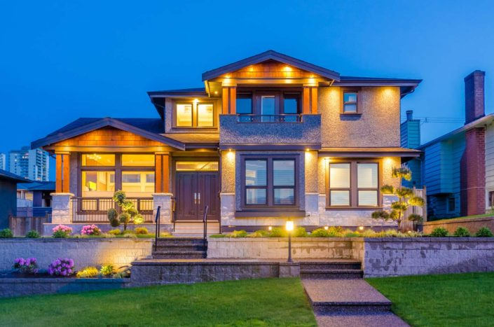 Two story family home with craftsman styling, pictured at dusk.
