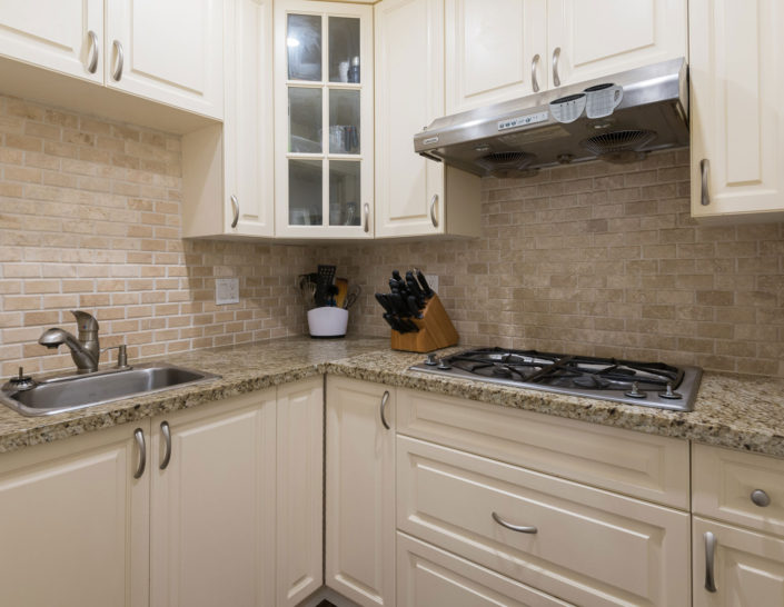 Corner of newly renovated kitchen with tile backsplash, stove, sink and marble countertops.
