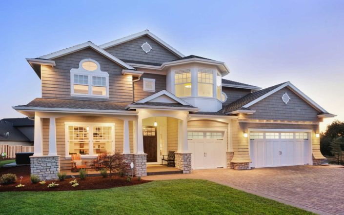 Large grey with white traditional home at dusk.