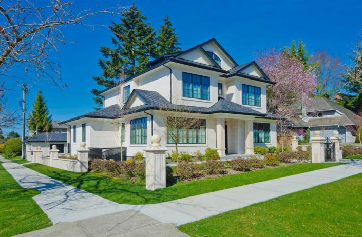Kitsilano style large new home with white stucco and peaked roofs.