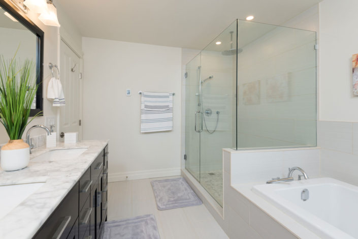 New bathroom with large glassed-in shower, tub and brown cabinets with white marble countertop.