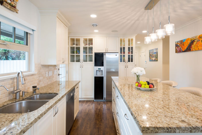Beautiful, newly renovated white kitchen with tan marble counter tops and built-in cabinets.