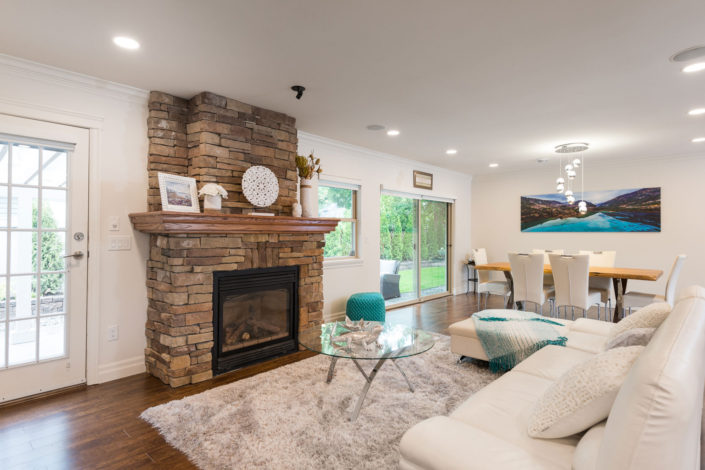 Freshly renovated living room with white decor and brown rock fireplace.