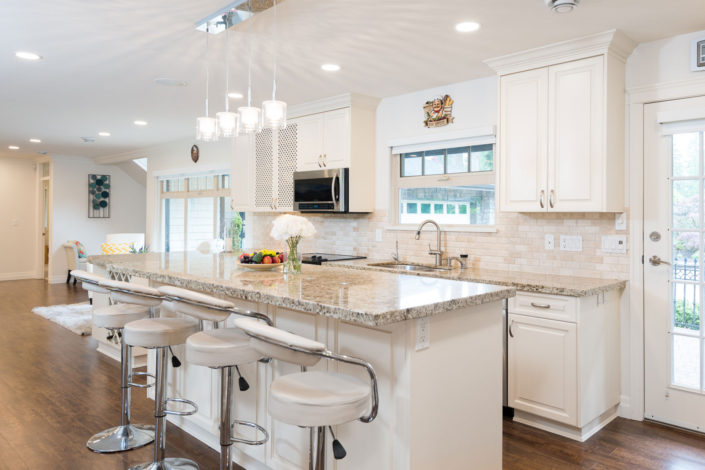 Beautiful, newly renovated white kitchen with white marble counter tops and white leather barstools.