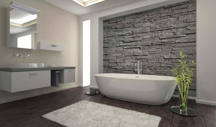 Beautiful modern bath with freestanding tub in front of rock wall.