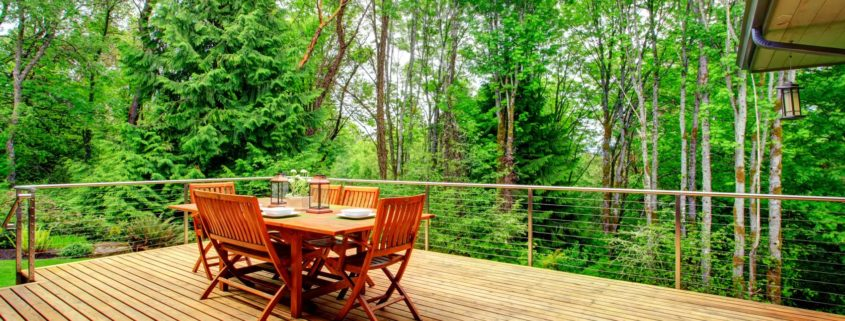 Large wood deck with wood table and chairs in woodsy backyard.