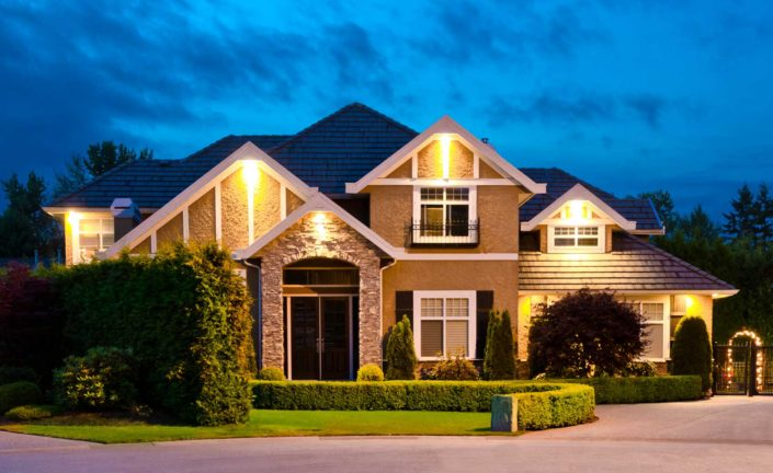 Tudor influenced executive home with outside lighting at dusk.