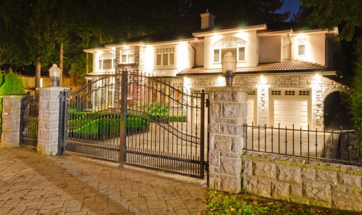 Large Vancouver style home with decorative metal and stone gate.