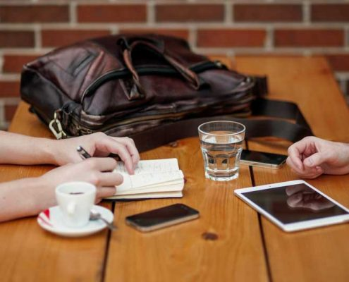 Meeting table top with coffee cups, cell phones, notebook and ipad and the arms of two attendees.