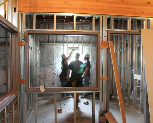 Three construction workers in a framed house in Vancouver house.
